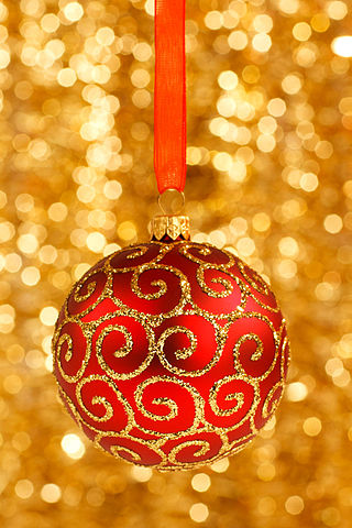 red Christmas bauble on blurred golden background